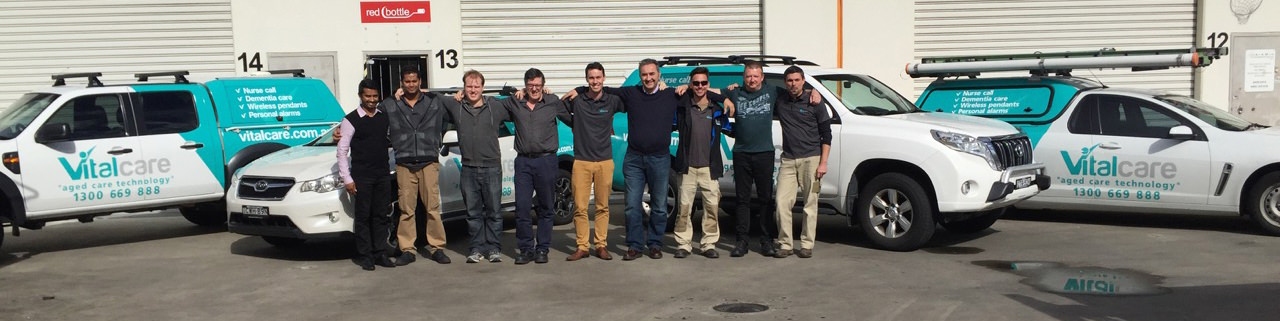 The Vitalcare Team standing with the fleet of Vitalcare vehicles